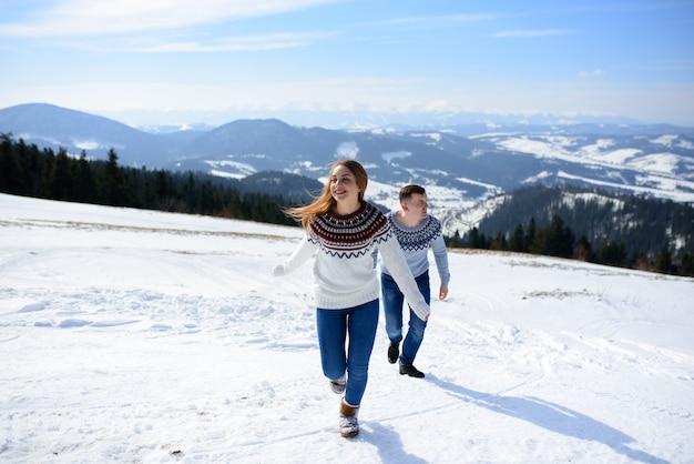 Jonge liefdevolle paar op een datum op de top van een besneeuwde berg
