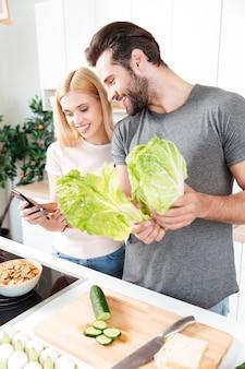 Jonge liefdevolle paar samen koken met behulp van mobiele telefoon