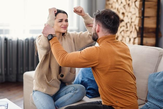Jonge liefdevolle vrouw ter ondersteuning van haar depressieve man tijdens psychotherapie sessie met counselor, vrije ruimte
