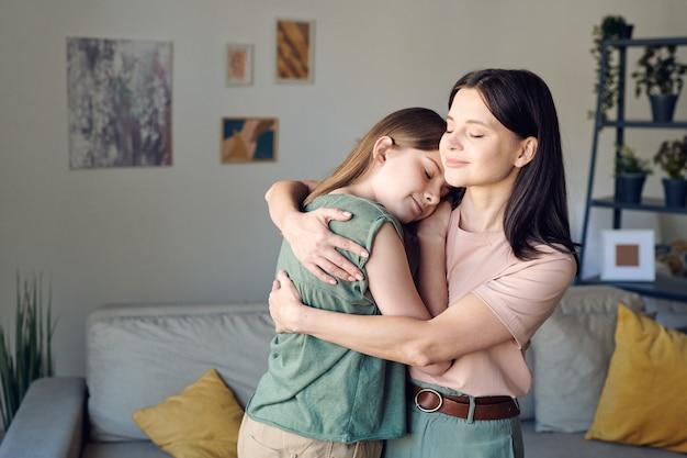 Jonge liefhebbende moeder die haar schattige aanhankelijke dochter omhelst in een thuisomgeving na terugkomst van zakenreizen of werk