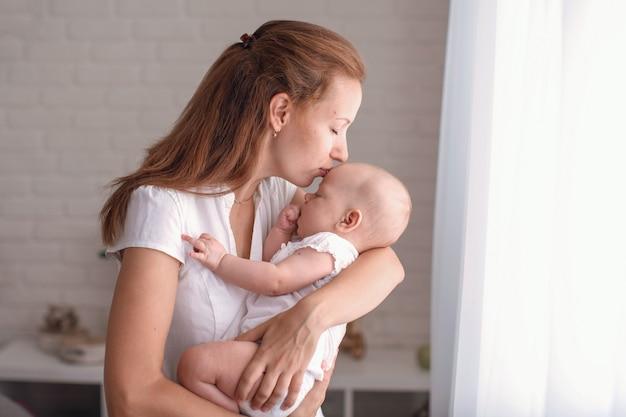 Jonge liefhebbende moeder knuffels en kust haar baby bij het slaapkamerraam.