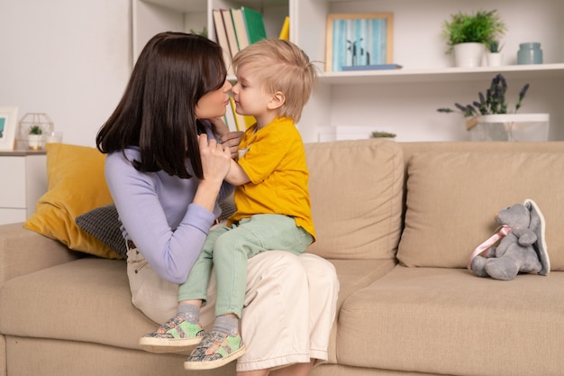 Jonge liefhebbende moeder zittend met zoon op knieën in de woonkamer en kuste hem
