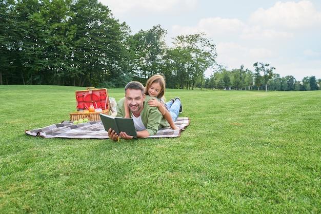 Jonge liefhebbende vader die tijd doorbrengt met zijn schattige dochtertje dat een boek leest tijdens een bezoek