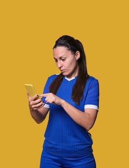 Jonge liefhebber van sportweddenschappen die haar smartphone in geïsoleerde muur met behulp van
