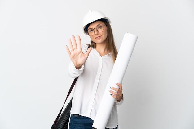 Jonge litouwse architect vrouw met helm en blauwdrukken bedrijf geïsoleerd op een witte achtergrond vijf tellen met vingers