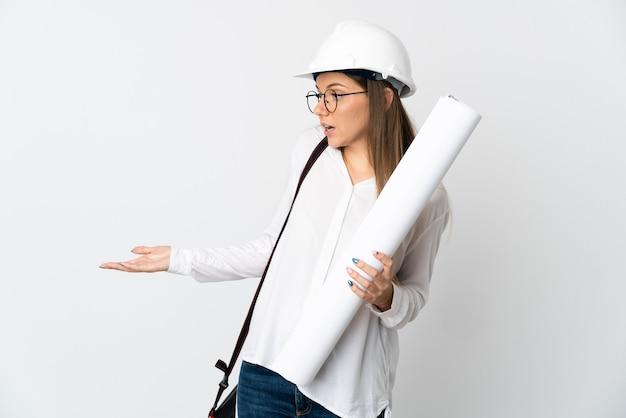 Jonge litouwse architect vrouw met helm en blauwdrukken geïsoleerd op een witte muur met verrassing expressie terwijl op zoek naar kant