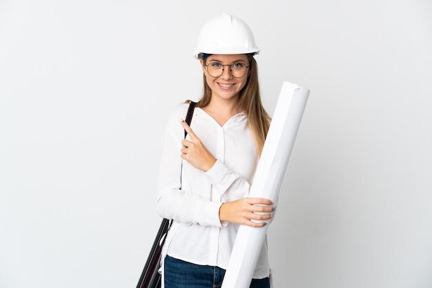 Jonge litouwse architectenvrouw met helm en bedrijfsblauwdrukken die op witte muur worden geïsoleerd die naar de kant wijzen om een product te presenteren