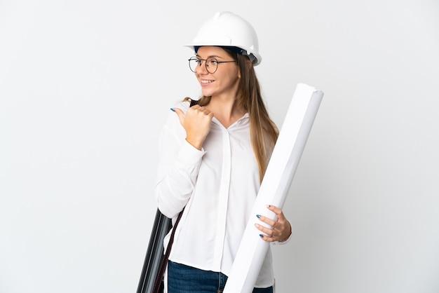 Jonge litouwse architectenvrouw met helm en blauwdrukken die op witte achtergrond worden geïsoleerd die naar de kant wijzen om een product te presenteren
