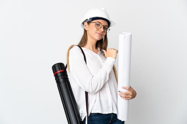 Jonge litouwse architectenvrouw met helm en blauwdrukken die op witte achtergrond worden geïsoleerd. trots en zelfvoldaan