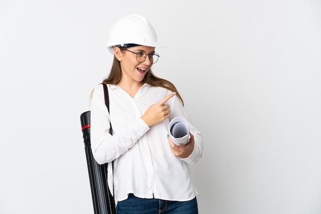 Jonge litouwse architectenvrouw met helm en blauwdrukken die op witte muur worden geïsoleerd die vinger naar de zij richten en een product voorstellen