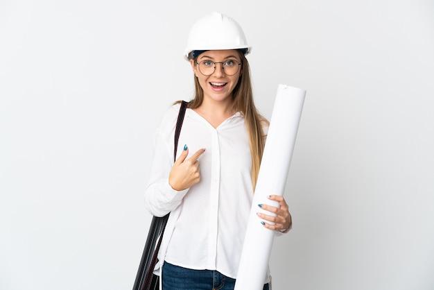 Jonge litouwse architectenvrouw met helm en blauwdrukken houden die op witte achtergrond met verrassingsgelaatsuitdrukking worden geïsoleerd
