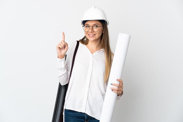 Jonge litouwse architectenvrouw met helm en blauwdrukken houden die op witte achtergrond worden geïsoleerd die en een vinger in teken van het beste opheffen