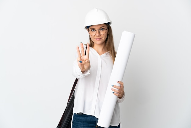 Jonge litouwse architectenvrouw met helm en blauwdrukken houden die op witte muur gelukkig worden geïsoleerd en drie met vingers tellen