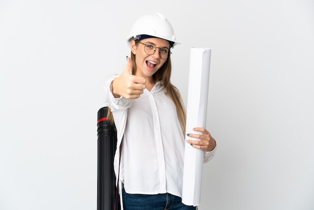 Jonge litouwse architectenvrouw met helm en blauwdrukken houden die op witte muur met omhoog duimen worden geïsoleerd omdat er iets goeds is gebeurd