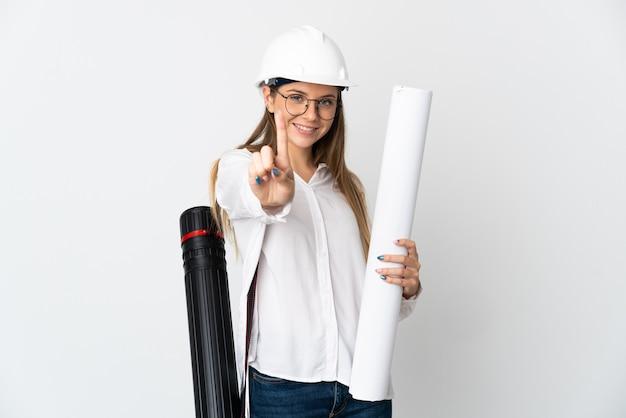 Jonge litouwse architectenvrouw met helm en blauwdrukken houden die op witte muur worden geïsoleerd die en een vinger opheft