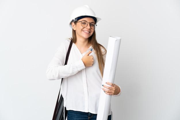 Jonge litouwse architectenvrouw met helm en holdingsblauwdrukken die op witte muur worden geïsoleerd die een duim omhoog gebaar geven