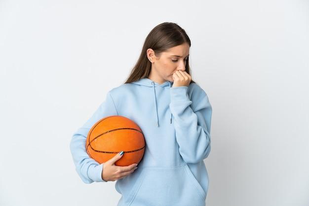 Jonge litouwse vrouw die basketbal speelt geïsoleerd op een wit oppervlak met twijfels
