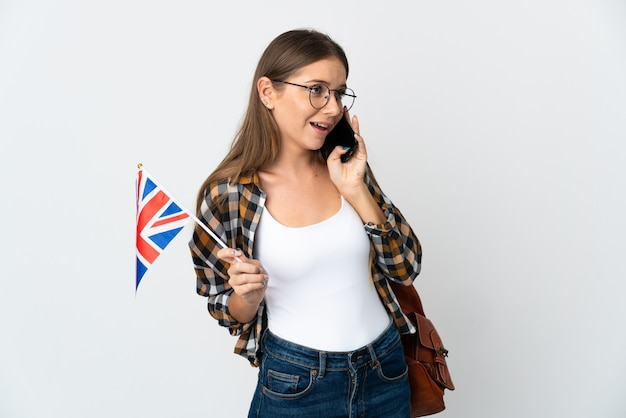 Jonge litouwse vrouw die een vlag van het verenigd koninkrijk houdt die op witte muur wordt geïsoleerd en een gesprek met de mobiele telefoon met iemand houdt