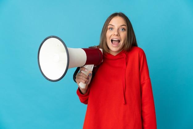 Jonge litouwse vrouw die op blauwe muur wordt geïsoleerd die een megafoon houdt en met verrassingsuitdrukking