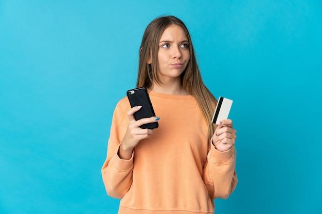 Jonge litouwse vrouw die op blauwe muur wordt geïsoleerd die met mobiel met een creditcard koopt terwijl het nadenken