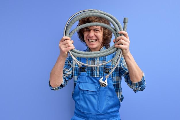 Jonge loodgieter man met slang en camera erdoor kijken, sterk zelfverzekerd sanitair ingenieur geïrriteerd