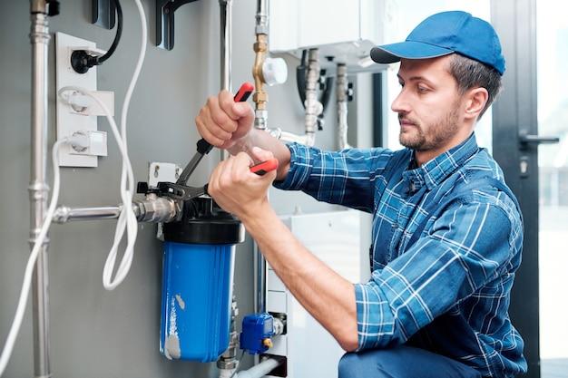 Jonge loodgieter of technicus in werkkleding met behulp van een tang tijdens het installeren of repareren van systeem van waterfiltratie