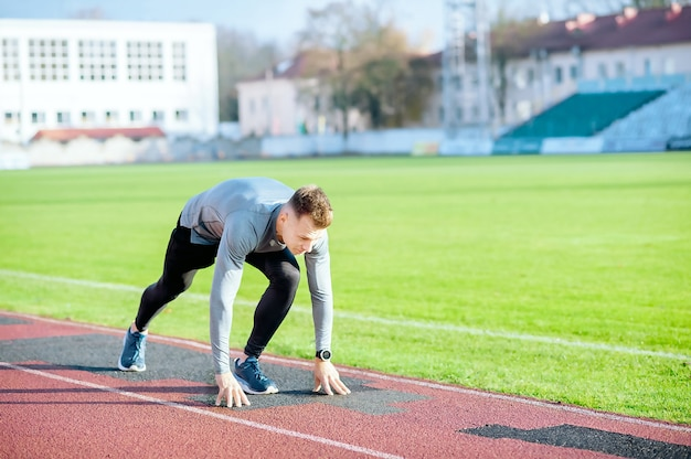 Jonge loper man in startpositie klaar om te rennen op het circuit van het stadion.