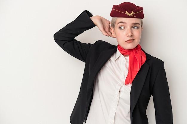 Jonge lucht gastvrouw blanke vrouw geïsoleerd op een witte achtergrond achterhoofd aan te raken, denken en een keuze maken.