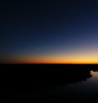 Jonge maan over de rivier in de schemering. heldere avondlucht na zonsondergang.