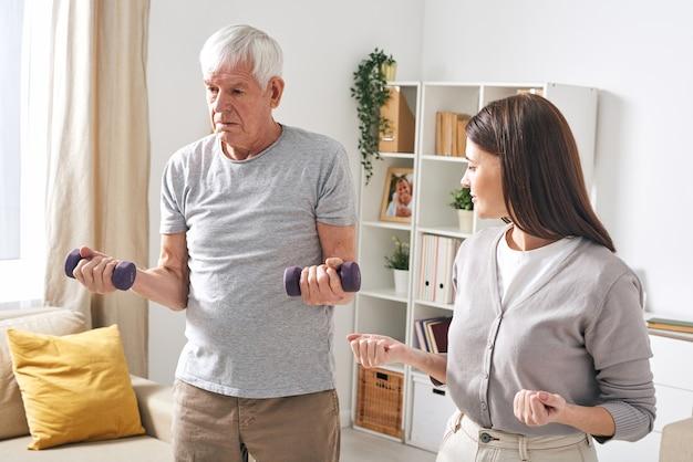 Jonge maatschappelijk werker die senior man laat zien hoe hij oefeningen met halters moet uitvoeren terwijl hij hem helpt om te revalideren