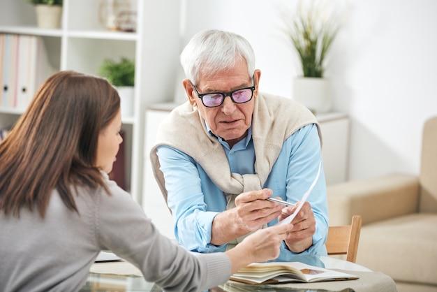 Jonge maatschappelijk werker of verzekeringsagent die vragen stelt aan senior man over punten van het papier tijdens thuisoverleg
