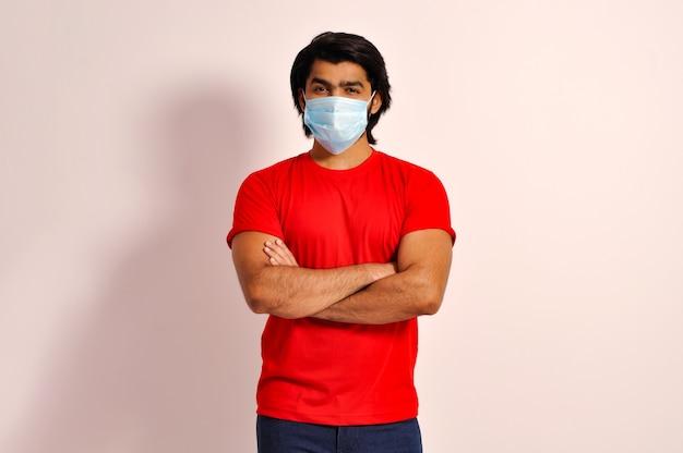 Jonge macho man met masker vouwen beide handen armen gekruist kijkend naar camera