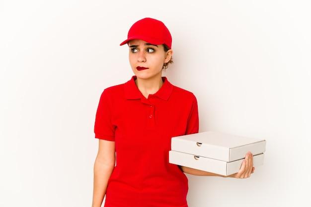 Jonge magere arabische pizzabezorger die achterkant van het hoofd aanraakt, denkt en een keuze maakt