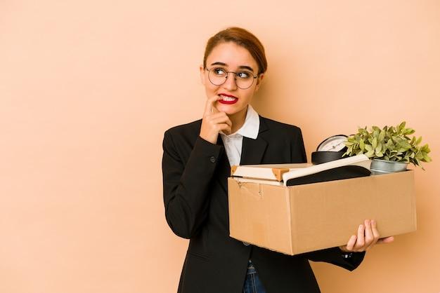Jonge magere arabische zakenvrouw bewegende baan geïsoleerd ontspannen denken aan iets kijken naar een kopie ruimte
