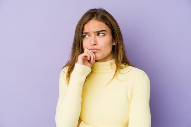 Jonge magere blanke meisjestiener op paarse muur, zijwaarts kijkend met twijfelachtige en sceptische uitdrukking.
