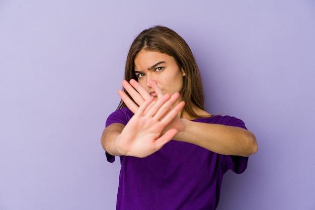 Jonge magere kaukasische meisjestiener op paars die een ontkenningsgebaar doet