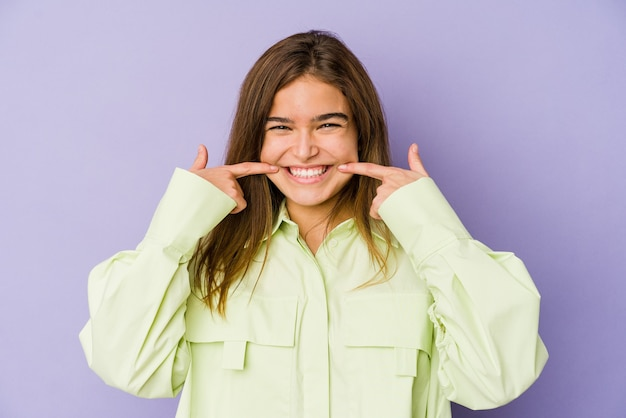 Jonge magere kaukasische meisjestiener op purpere glimlach als achtergrond, wijzende vingers naar mond.