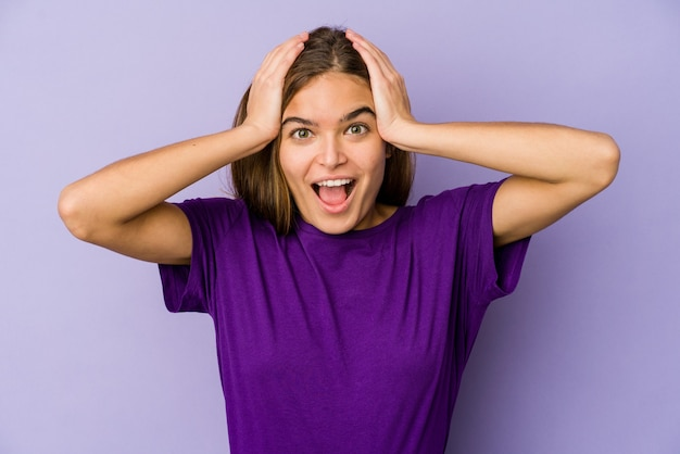 Jonge magere meisjestiener op paarse muur schreeuwen, erg opgewonden, hartstochtelijk, tevreden met iets