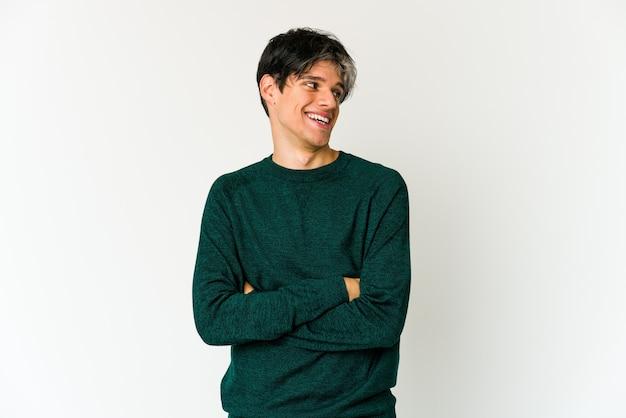 Jonge magere spaanse mens die zelfverzekerd met gekruiste armen glimlacht