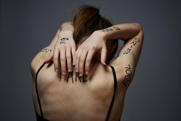 Jonge magere vrouw met beledigingen op het lichaam inscripties, slechte woorden, depressieve toestand, eenzaamheid