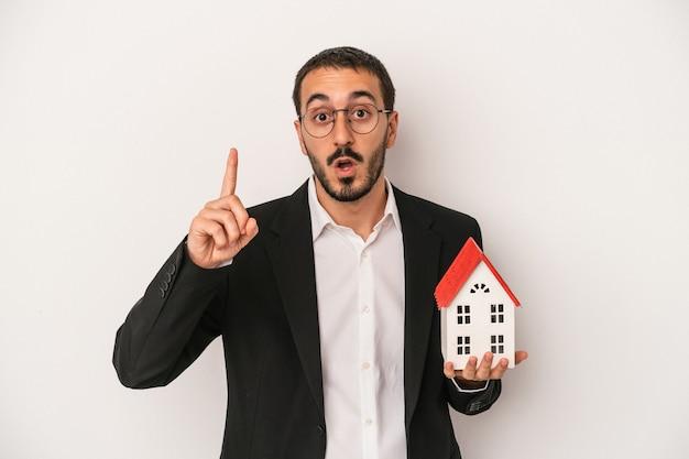 Jonge makelaar man met een model huis geïsoleerd op een witte achtergrond met een idee, inspiratie concept.