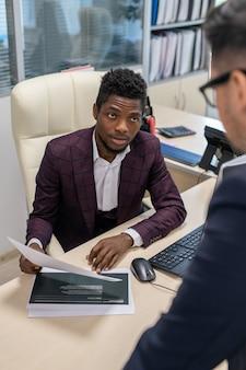 Jonge makelaar van afrikaanse etniciteit die financieel document toont aan baas