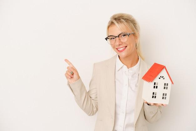 Jonge makelaarsvrouw die een huismodel houdt dat op witte achtergrond wordt geïsoleerd glimlacht en wijst opzij, die iets tonen bij lege ruimte.