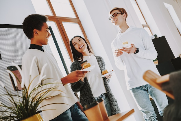Jonge makers drinken koffie op kantoor met vrienden.