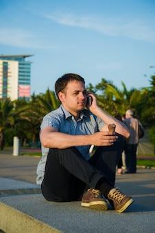 Jonge man aan de promenade die een ijsje eet en zijn telefoon gebruikt, misschien is hij vrijgezel of wacht hij op iemand