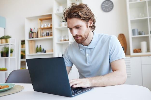 Jonge man aan de tafel zitten en thuis lap top computer gebruikt