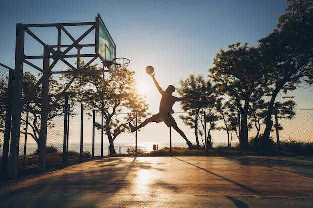 Jonge man aan het sporten, basketbal spelen bij zonsopgang, silhouet springen