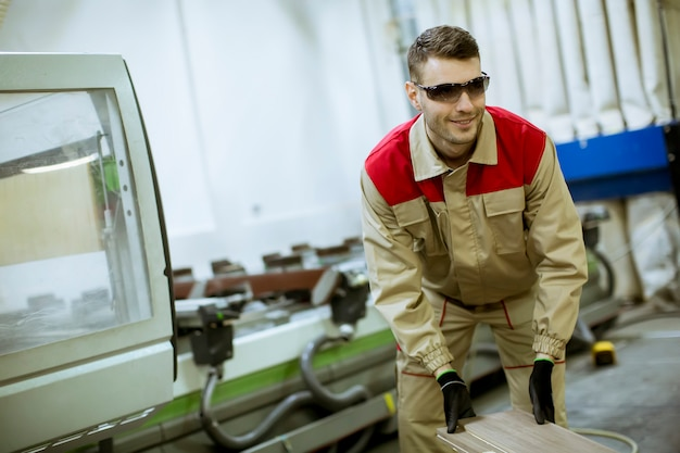 Jonge man aan het werk in de meubelfabriek