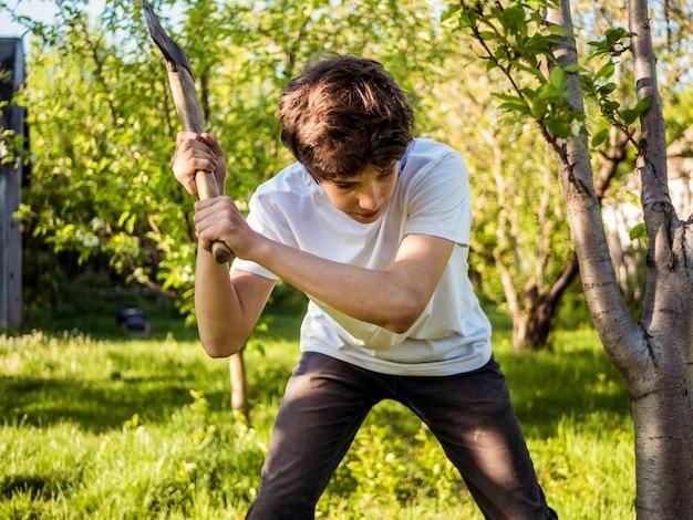 Jonge man aan het werk in de tuin met bijl in de buurt van de boom