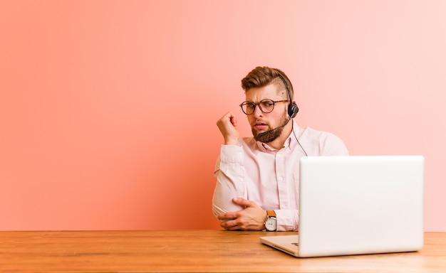 Jonge man aan het werk in een callcenter aanraken achterkant, denken en het maken van een keuze.